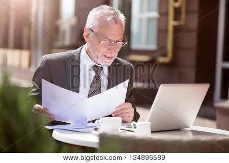 Pleasant work. Senior delighted businessman sitting at the table and using laptop while working with papers