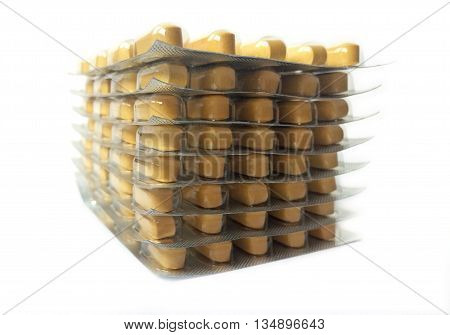 Stacked yellow medication blisters on white background