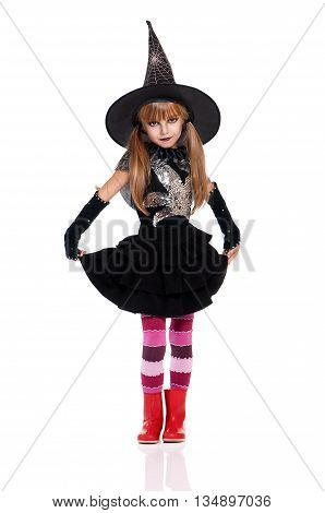 Little girl dressed like witch for Halloween party. Studio portrait isolated over white background.