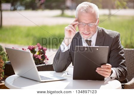 Like my work. Pleasant smiling senior man sitting at the table and holding folder while being involved in work