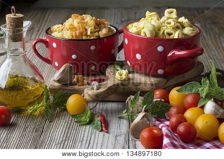 Still life Italian pasta. Tortellini in the form of hearts on a cutting board with olive tree surrounded by colored cherry tomatoes, sharp colored peppers, oregano and olive oil. selective focus