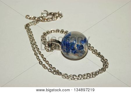 Frusto ball shaped pendant with blue petals inside the epoxy resin crystal with a chain.