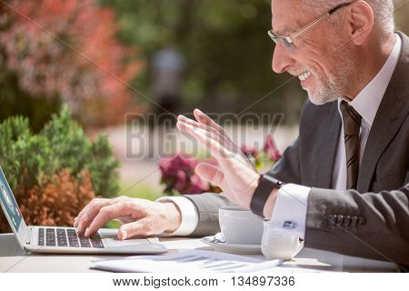 Glad to hear you. Pleasant cheerful smiling senior man using laptop and talking through the internet while sitting at the table