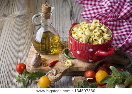 Homemade pasta. Traditional Italian tortellini in a red ceramic saucepan with white polka dots on the board of the olive tree surrounded by tomatoes, peppers, greens, herbs and olive oil. selective focus