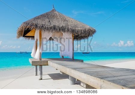 Tropical open hut on the beach on Maldivian white sand beach with view of the blue ocean lagoon