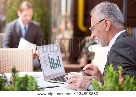 Modern life. Pleasant concentrated man using laptop and sitting at the table while another person resting in the background