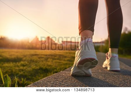 Close up of woman running shoes on sunset.