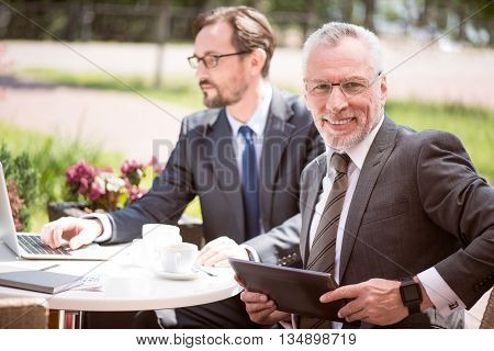Feel positively. Cheerful handsome senior man holding tablet and sitting at the table while his colleague using laptop in the background