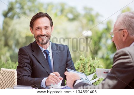 Share positivity. Delighted cheerful handsome smiling man working and expressing gladness while sitting at the table with his colleague outside