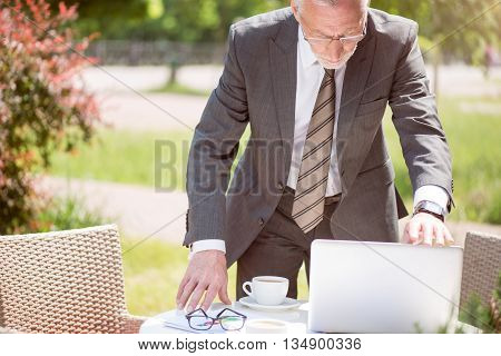Almost done. Pleasant serious senior man standing near tablet and holding laptop while being involved in work