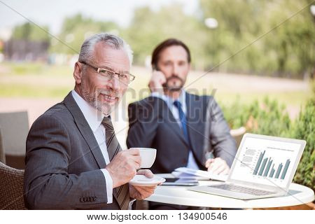 Have a nice rest. Pleasant handsome smiling senior man sitting at the table and drinking coffee while his colleague stalking on cell phone in the background