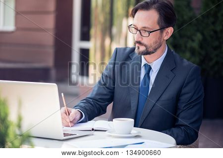 Involved in important task. Pleasant concentrated man sitting at the table and making notes while working