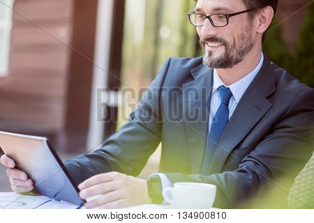 Express yourself. Pleasant handsome overjoyed man sitting at the table and using tablet while feeling glad