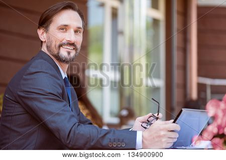 Get a great relaxation. Positive smiling handsome man sitting at the table and holding tablet while resting in the cafe