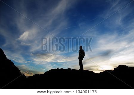 Hiker standing and watching the sunset, after a tiring trekking day