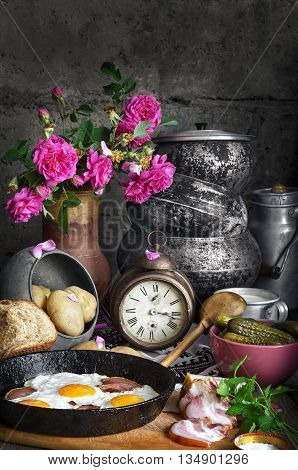 Bacon and eggs in an old pan on the Board. Chopped bacon and cucumbers in a bowl. In the background old iron pots broken clock and a bouquet of tea roses in an old jug.
