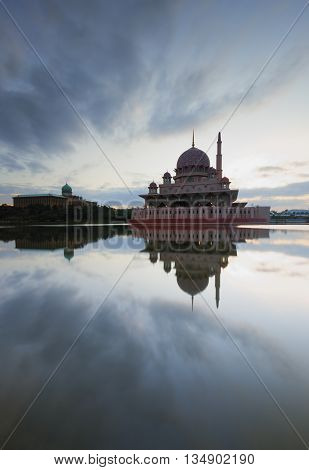 A portrait shot of a mosque with beautiful reflection of clouds.