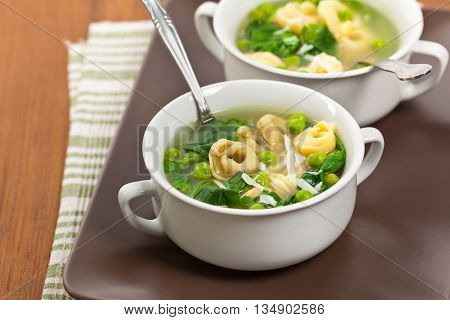 Tortellini Soup with Peas and Spinach. Selective focus.