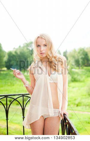 Girl in white lingerie on the balcony