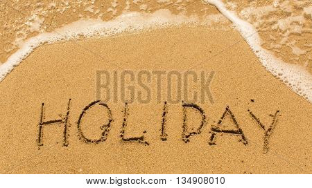 Holiday - inscription on sand beach with the soft wave.