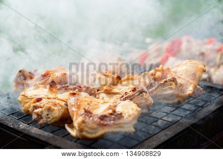 Chicken legs being fried on grill outdoors