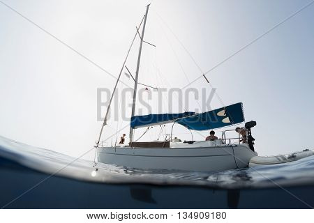 Split shot of the sail boat with people on surface and its underwater view