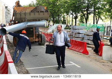 MOSCOW, RUSSIA - MAY 15, 2016: Laughing man with a smartphone and a black bag on a construction site. Reconstruction of the roadway within the city beautification program My Street in Moscow.