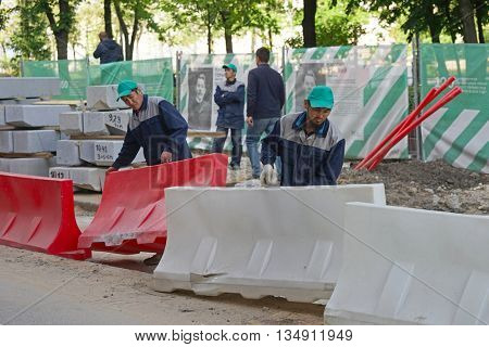 MOSCOW, RUSSIA - MAY 15, 2016: Asian workers install a road fencing. Reconstruction of the roadway within the city beautification program My Street in Moscow.