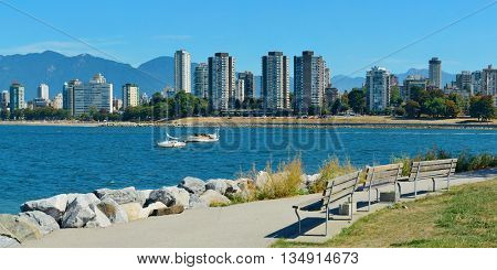 Vancouver city skyline at waterfront with bench in park