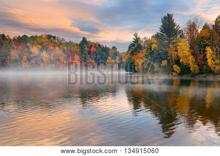 Lake fog sunrise with Autumn foliage and mountains in New England Stowe
