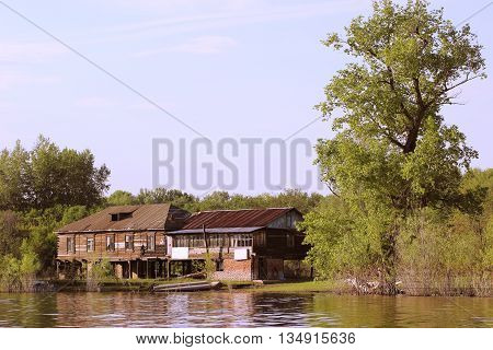 The old house at the water's edge on the banks of the river surrounded by wildlife