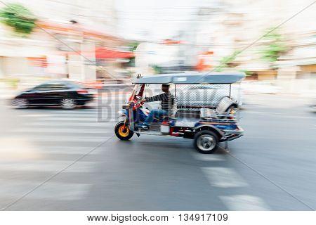 BANGKOK THAILAND - APRIL 24: Man riding tuk-tuk on April 24 2016 in Bangkok Thailand.