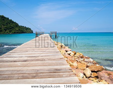 Jetty wooden bridge into blue sea and sky. Pier over water. Vacation And tourism concept. Tropical resort. Jetty on Koh Kood Island Thailand.