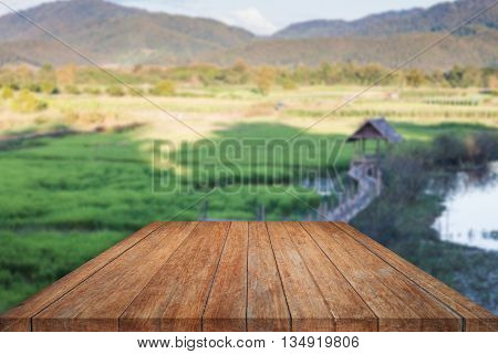 Perspective top wooden with green field blurred background, stock photo
