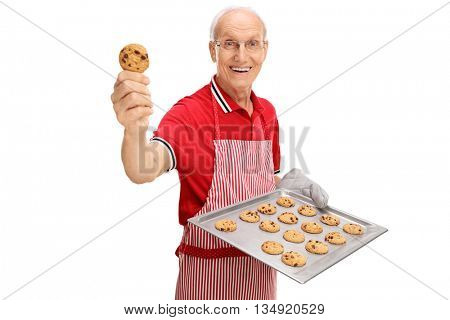 Cheerful senior showing his homemade chocolate chip cookies isolated on white background