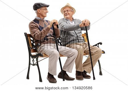 Two elderly men sitting on a wooden bench and talking to each other isolated on white background