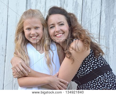 Happy mother hugging young blond daughter why whitewashed barn.