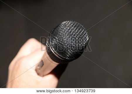 professional microphone in hand as a tool for sound recording
