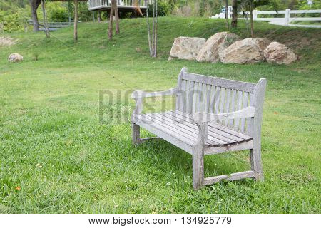 diagonal wooden bench in green garden lawn for resting and relax