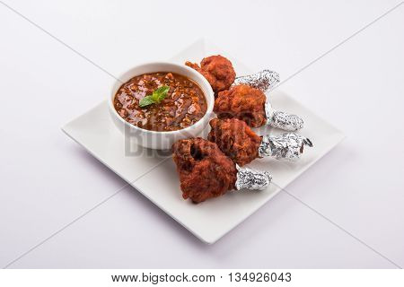 chicken lolipop, chicken winglet, tandoori chicken. Famous indian non veg dish, roasted chicken covered with silver foil, served with spicy chutney, indian chinese appetizer