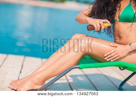 Attractive brunette on the beach. Young woman in swimwear using suntan oil on the beach.