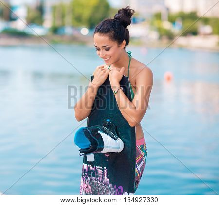Young attractive brunette woman posing with wakeboard on the beach.
