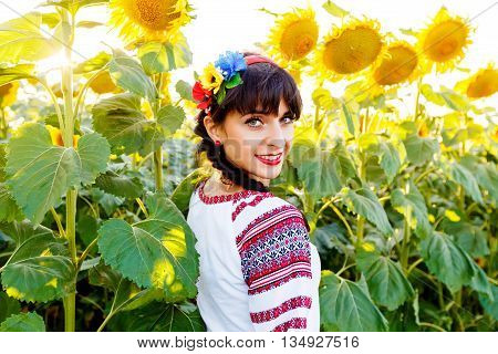 Beautiful young woman in national ukrainian blouse embrodery looking to camera on a sunflower plant at sunset backlight.