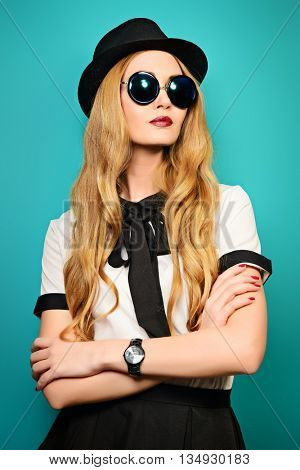 Beautiful fashionable young woman wearing elegant blouse, hat and sunglasses. Studio shot over aquamarine background.
