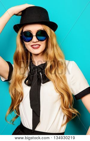 Portrait of a beautiful smiling young woman wearing pretty blouse, hat  and sunglasses. Studio shot over aquamarine background.