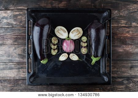 Whole And Sliced Eggplants On Baking Tray