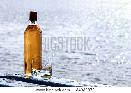 Bottle of whiskey and tumbler on the shore of lake