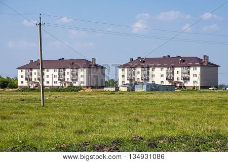 Village Morshanskoe Kargatskiy rayon Novosibirskaya oblast Siberia Russia - June 12 2016: new modern three-storied apartment house on the outskirts of the village