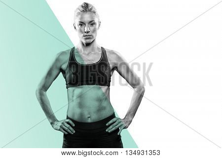 Female athlete standing with hand on hip against colored background