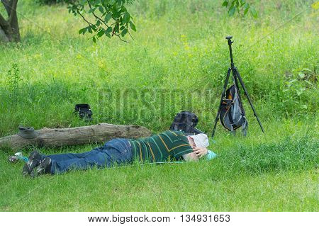 Tired outdoor photographer having rest in the herbs